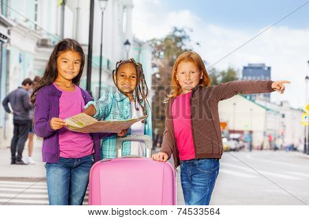 Beautiful girls stand with map and luggage in city
