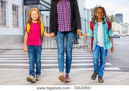 Two kids with woman walking on the street