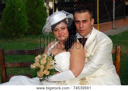 Young bride and groom couple posing for the camera outside