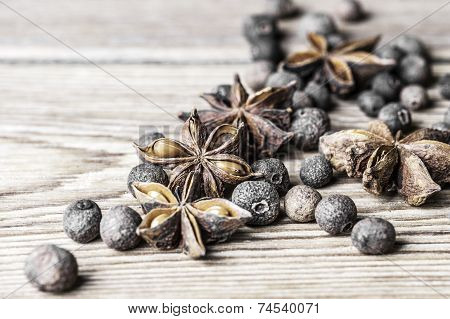 Allspice peas and the star anise on a wooden background