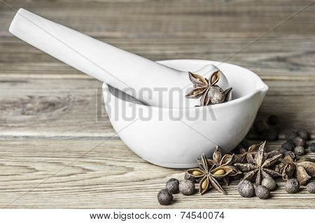 Allspice peas, the star anise and the porcelain mortar with pestle on a wooden background