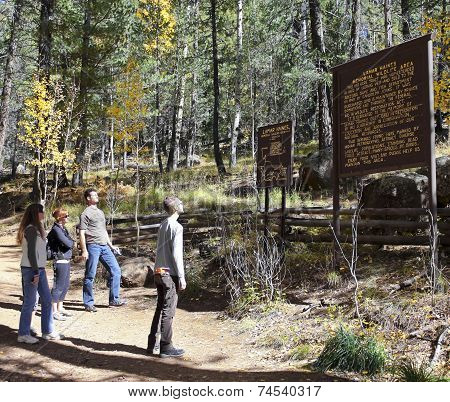 A Group Of Hikers Read A Wildlife Area Sign