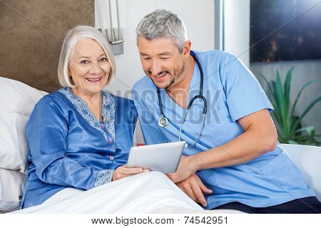 Portrait of happy senior woman using tablet PC with caretaker in bedroom at nursing home