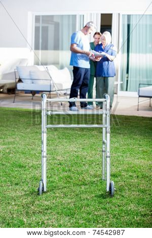 Walking frame on lawn with caretakers and senior woman in background at nursing home
