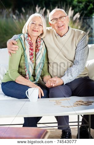 Portrait of happy senior couple sitting arm around on couch at nursing home porch