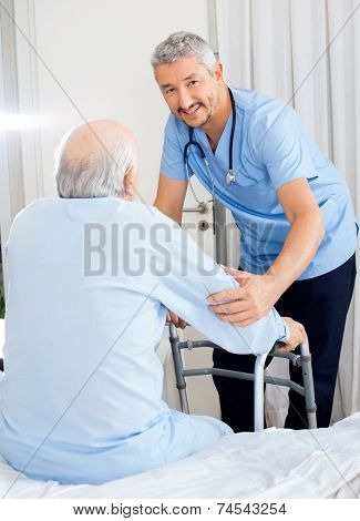 Portrait of smiling male caretaker helping senior man with walking frame in bedroom at nursing home