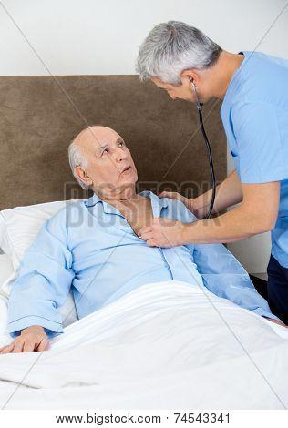 Male caretaker examining senior man with stethoscope in bedroom at nursing home