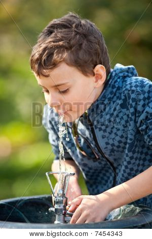 Cute Kid Drinking Water In A Park