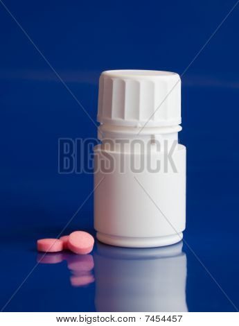 White Bottle With Pink Tablets On A Blue Background