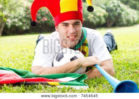 soccer fan lying on green grass