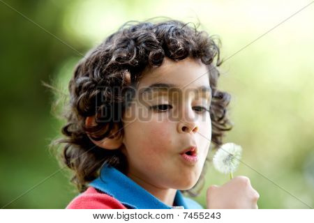 Kid Blowing A Dandelion