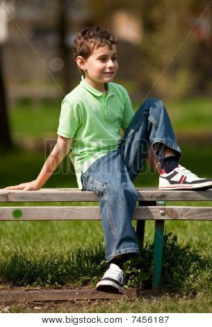 Cute Little Boy Sitting On A Bench