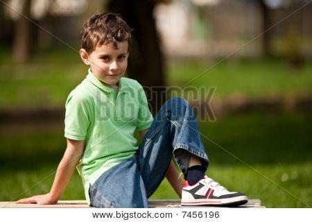Cute Little Boy Sitting On A Bench