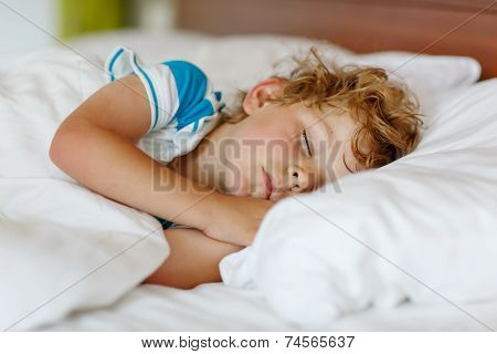 Little Blond Boy Sleeping In His Bed.