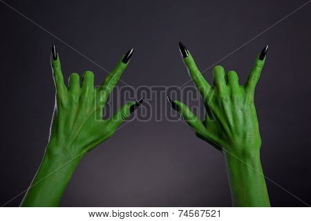Green monster hands with black nails showing heavy metal gesture, Halloween theme