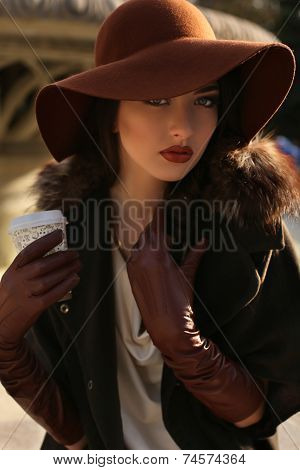 Portrait Of Beautiful Lady In Elegant Coat And Hat With Cup Of Coffee