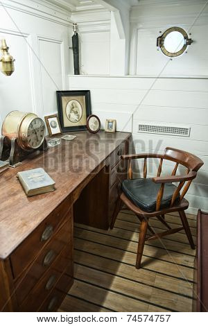 GREENWICH, LONDON - APRIL 06: Desk in Interior of Ship Quarters in Historical Cutty Sark Vessel (Museum Ship) with Historical Artifacts and Porthole on 25 April 2012.