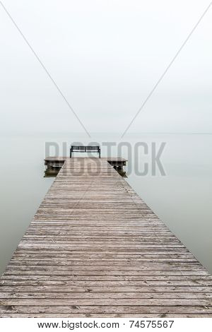 Jetty In Foggy Weather With Bench At End