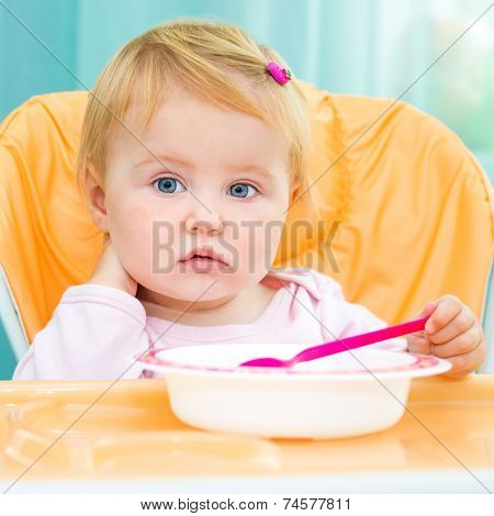 cute one year old girl in a highchair for feeding with a spoon and a plate in the kitchen