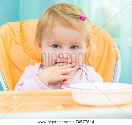 cute one year old girl in a highchair for feeding with a spoon and a plate  at home