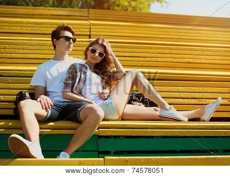 Young Modern Stylish Hipsters Couple Rest In Bench City Park, Sunny Portrait Couple Teenagers In Lov