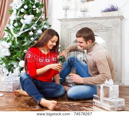 Young Happy Smiling Couple By The Cristmas Tree