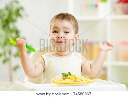 one year old kid boy in a highchair for feeding with a fork and