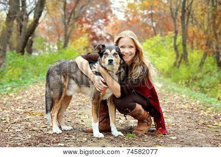 Woman And Dog In Woods In Autumn