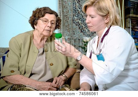 Senior woman is visited  by her doctor or caregiver at home.