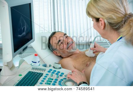 Doctor is using ultrasound machine to scan the heart of a senior male patient