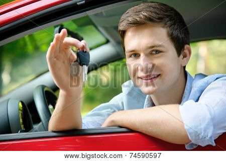 teenager sitting in new car and shows the keys