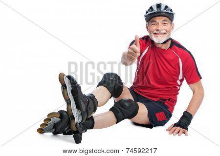senior man goes inline skating and shows thumbs up