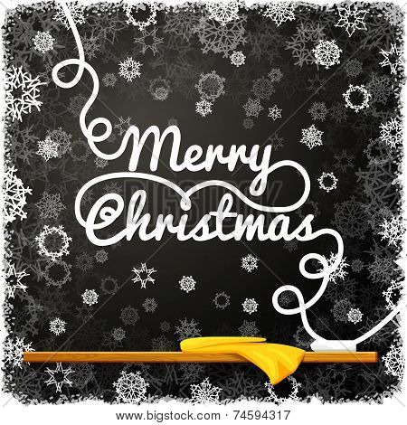 Merry christmas message, written on the black school chalkboard with curl lettering.