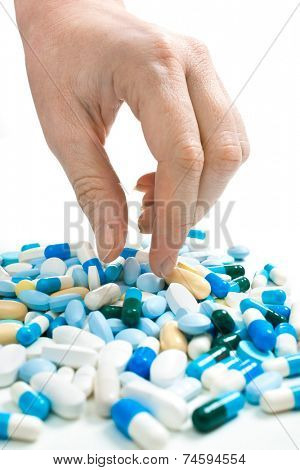 hand taking pills from the heap of different medications
