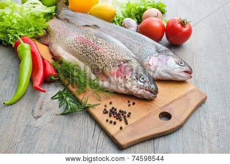 fresh trout, vegetables and spices on a cutting board