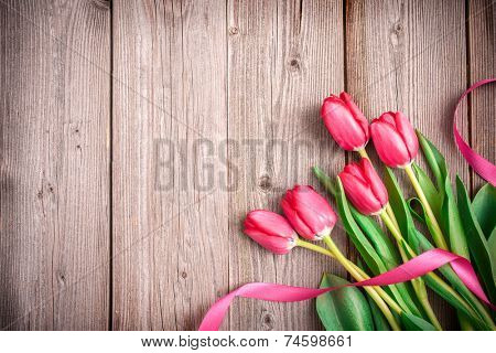 Pink tulips with a bow on wooden background with space for text