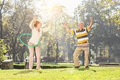 picture of hula hoop  - Mature couple exercising with hula hoops in park on a sunny day - JPG