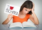 picture of hate  - Girl studying and holding a sign with the words I hate school - JPG
