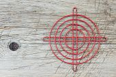 foto of crosshair  - Red metallic crosshair on an old wooden surface - JPG