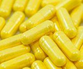 image of enzyme  - Yellow Drug Capsules pills closeup macro background - JPG