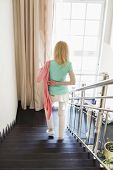 foto of down jacket  - Rear view of woman wearing jacket while moving down steps at home - JPG