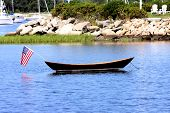 foto of dory  - American flag hanging off the stern of a wooden dory in a quiet cove in summer - JPG
