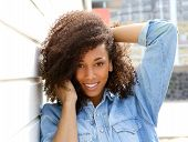foto of african american hair styles  - Close up portrait of a happy african american woman smiling outdoors with hand in hair - JPG
