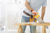 stock photo of sawing  - Midsection of man sawing wood in new house - JPG