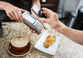 picture of over counter  - Cropped image of customer paying through mobilephone over electronic reader at cafe counter - JPG