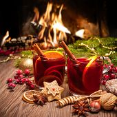 foto of christmas spices  - Two glasses of  mulled wine with christmas decoration at romantic fireplace - JPG