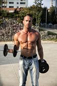 stock photo of hunk  - Gorgeous Shirtless Hunk Man Lifting Weights Outdoor - JPG