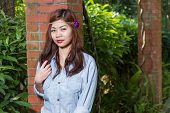picture of filipina  - Pinoy woman in a green garden on farm leaning against brick pillar - JPG