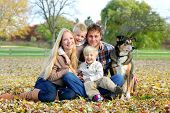 stock photo of puppies mother dog  - A happy family of four people including mother father young child and toddler brother are sitting outside in the fallen maple leaves with their pet German Shepherd dog on an Autumn day - JPG