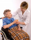 pic of crippled  - Health care worker and elderly woman in wheelchair needs help - JPG